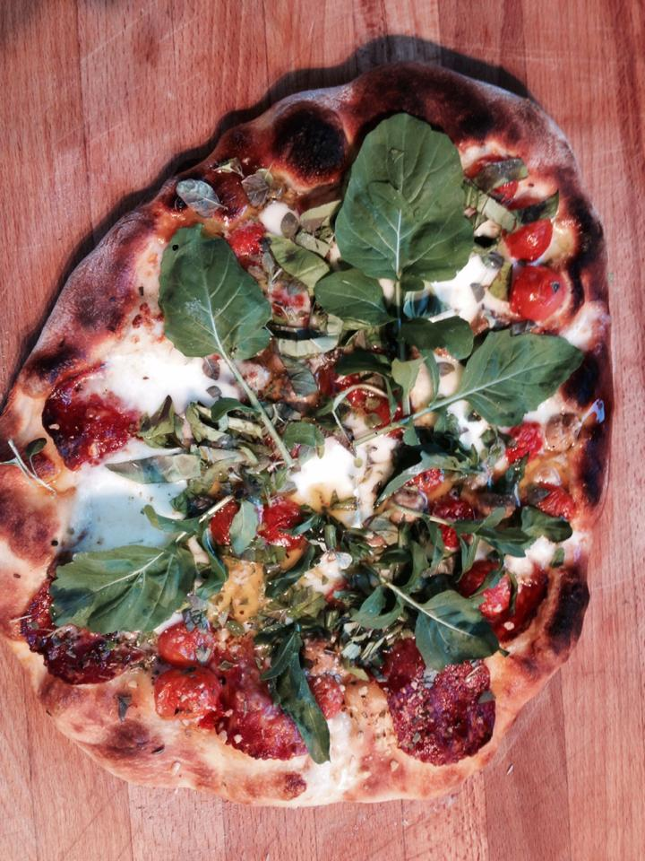 Pizza avec tomates herbes roquette de mon jardin et mozzarella frais sopressata et champignons marinés